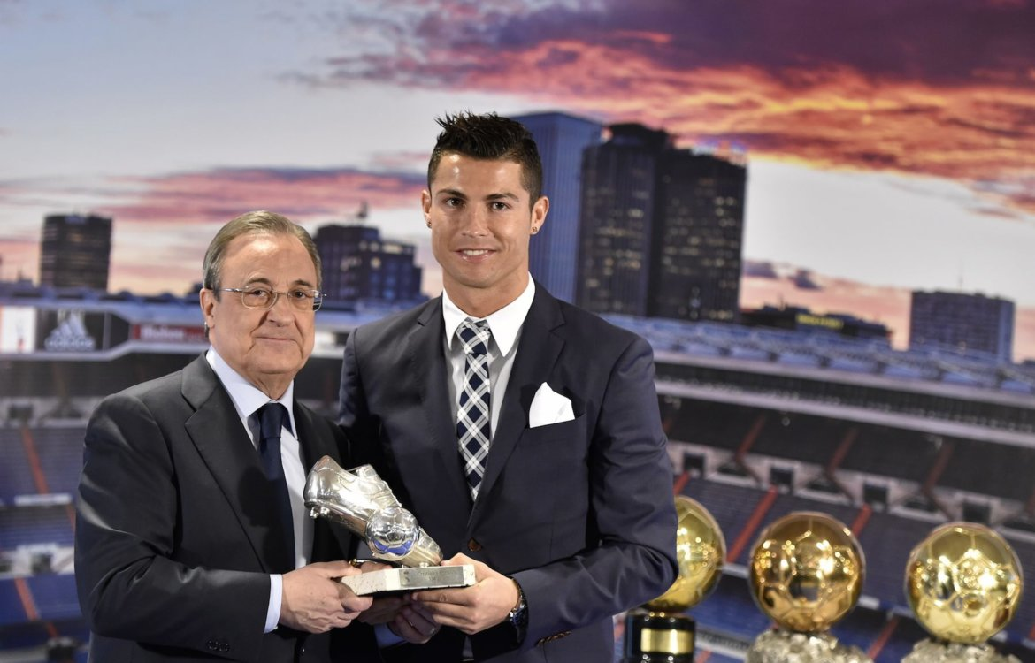 Real Madrid's forward Portuguese Cristiano Ronaldo (R) receives a trophy fom his club's president Florentino Perez after becoming Real Madrid's all-time leading scorer at the Santiago Bernabeu